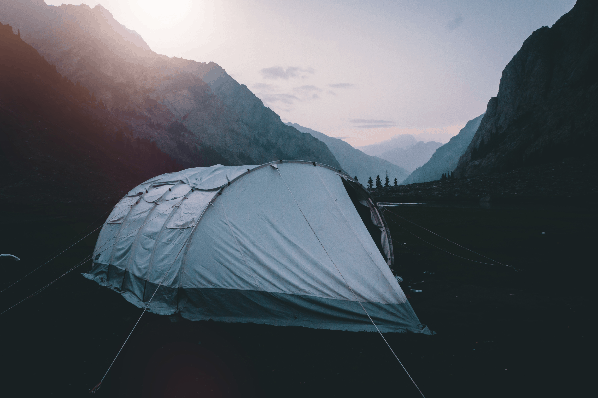 white tent in the middle of mountains