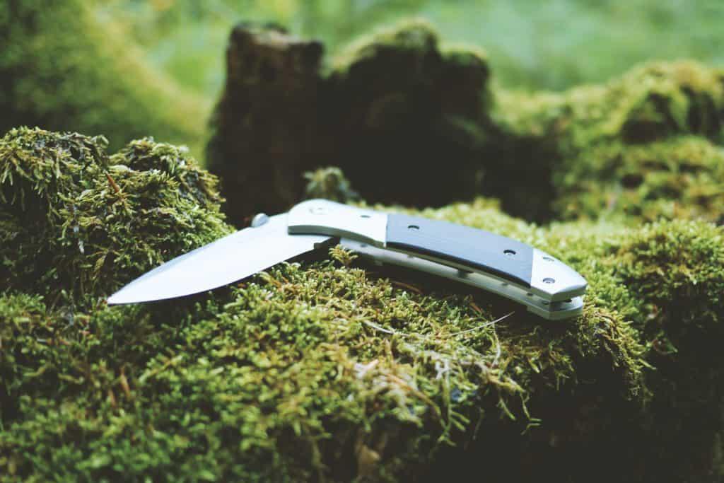 open folding knife sitting on moss