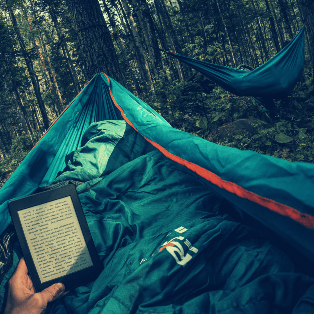 person in hammock reading kindle