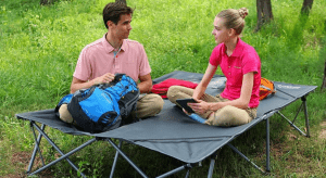 two people sitting on cot in outdoors