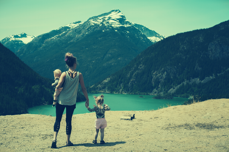 women with two children in front of lake and mountains