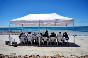 family sitting under canopy on beach