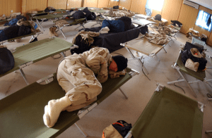 army man sleeping on side in cot