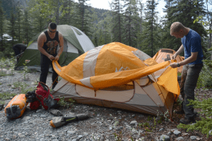 men setting up rainfly on tent outdoors