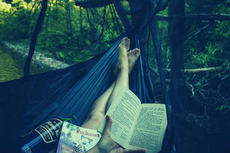 person reading book inside hammock with bug net