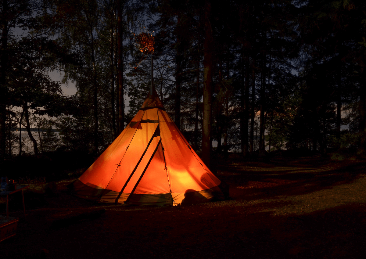 teepee shaped tent lit up outdoors