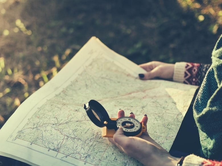 girl holding compass and map