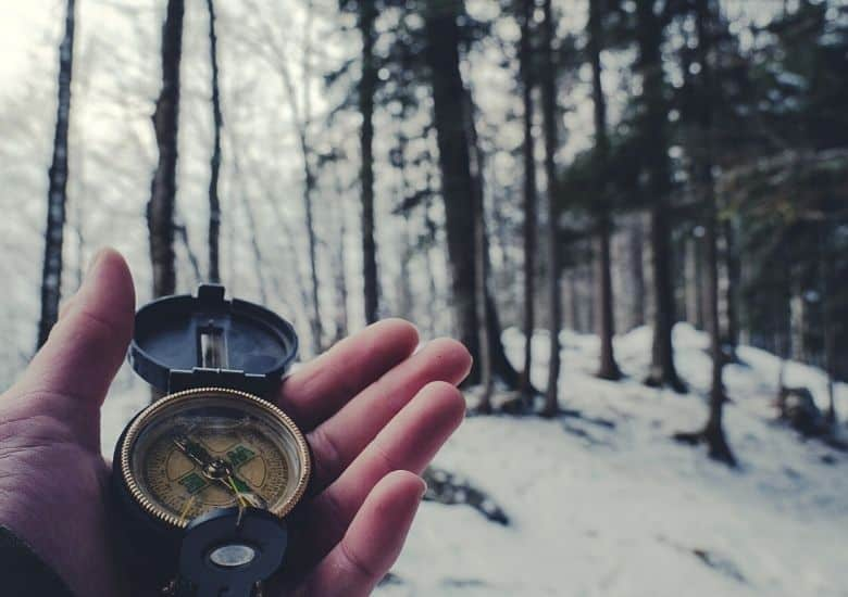 hand holding compass in winter woods
