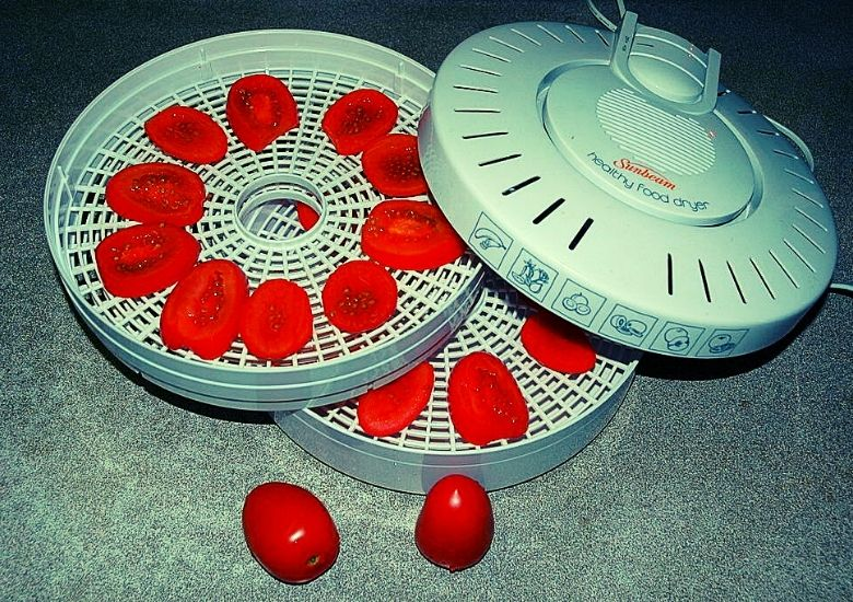 dehydrator taken apart with tomatoes inside