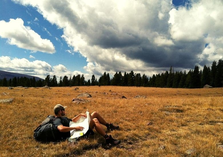 man in open field sitting with map